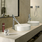 AXOR Starck Organic bathroom mixers next to wash bowls