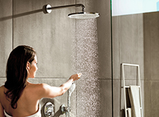 Woman showering with Croma 280 overhead shower.