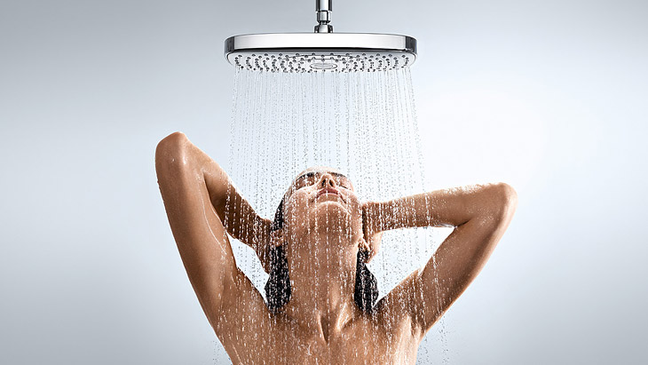 Woman under a Raindance Air overhead rain shower heads