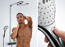 Man enjoys a shower with the Raindance Select Showerpipe E 300 – and switches the jet types of the hand shower at the touch of a button.