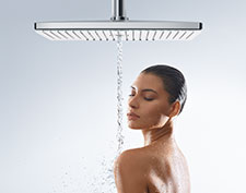 Woman under a Hansgrohe overhead shower.