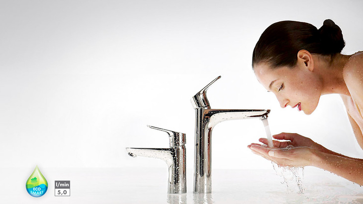 Woman leaning over a Focus basin mixer.