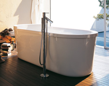 Free-standing bath tub by Philippe Starck with free-standing mixer alongside.