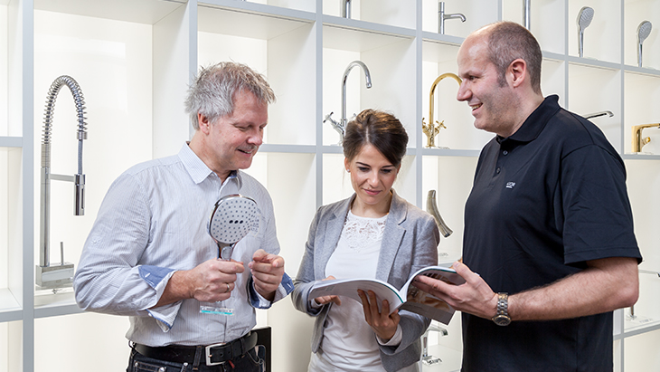 A training manager explains technical details of Hansgrohe products.