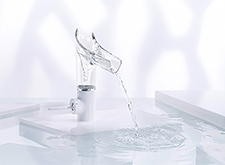 Single-hole faucet with open glass spout.