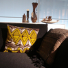 The cushion with the yellow pattern is perfectly accentuated on the dark sofa. As seen at Interluebke.