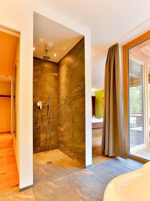 配有天然石材表面和镀铬龙头的淋浴房。