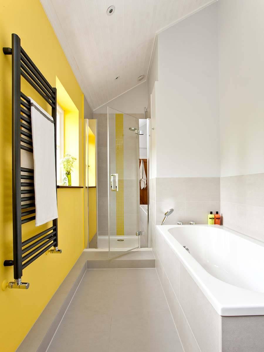 带浴缸和淋浴房的令人愉悦的日光黄色浴室设计。