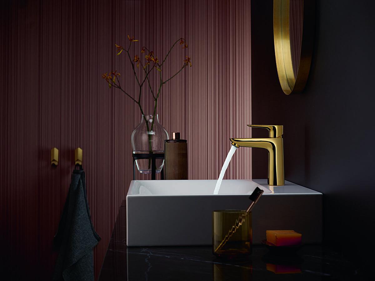 白色台盆上闪亮的金色浴室龙头。
