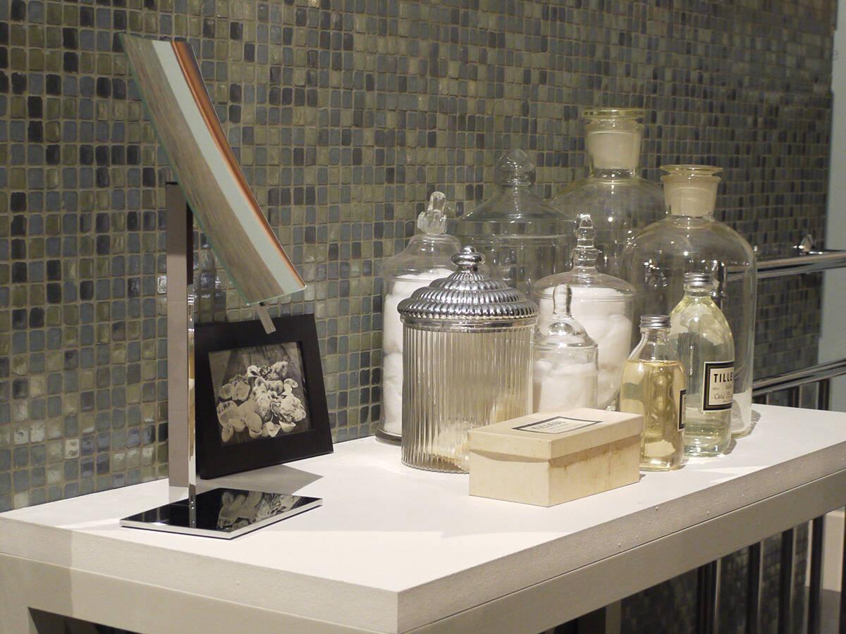 玻璃制浴室配件:化妆台上的镜子和玻璃杯。